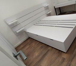 Белая кровать и стол в спальне